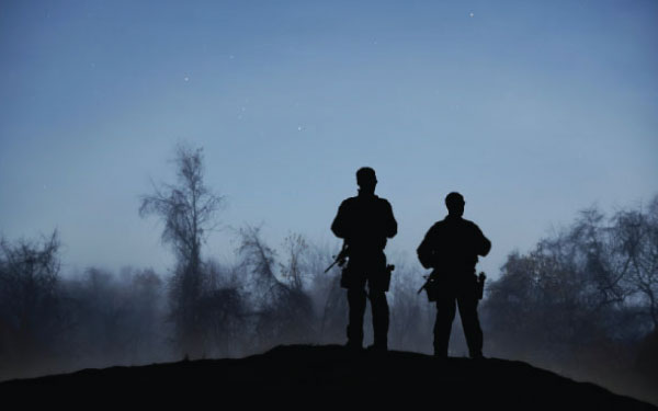 Two security personnel standing guard at dawn