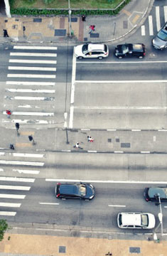 Bird's Eye View Of A Public Roadway With Cars Passing By and People Walking On The Sidewalk