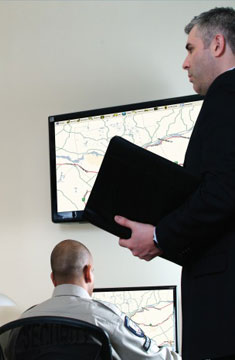 Travel Manager Working With Security Specialists To Monitor Travelers on Maps Displayed on Digital Screens